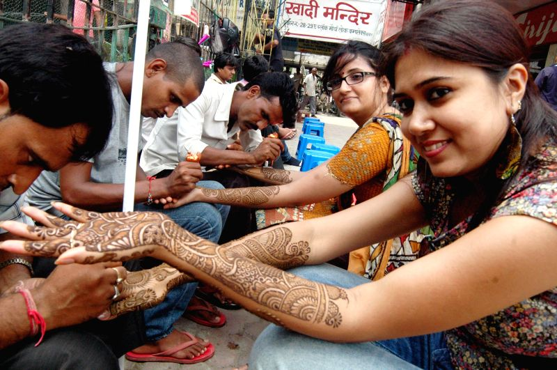 Women apply `mehndi'  on their hands on the eve of `Teej` in Patna on Aug 27, 2014.