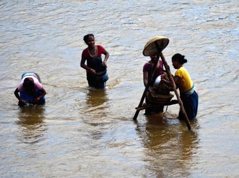 Women busy in mining sand from Singra River at Hahim in South Kamrup district of Assam on July 19, 2016.