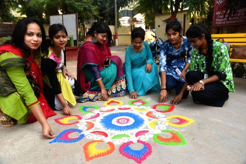 Women busy making 'rangoli' ahead of Diwali in Patna.
