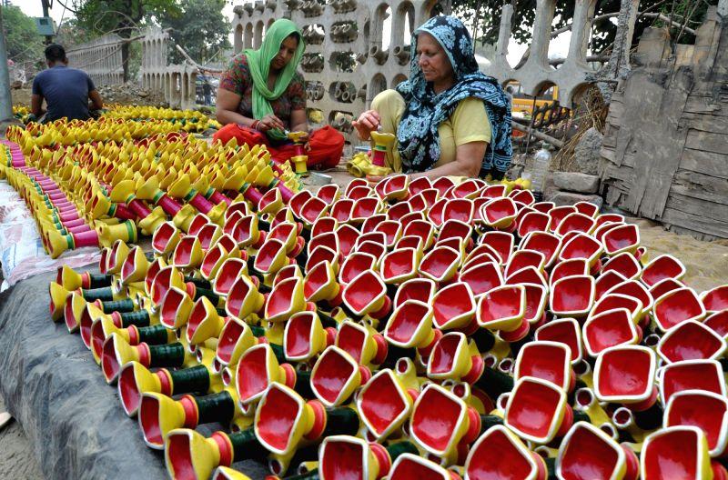 Women busy painting earthen lamps ahead of Diwali in Amritsar.