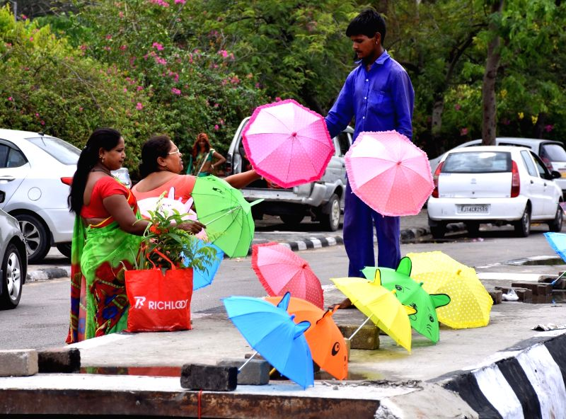Women buy bright-colored umbrellas during the monsoon season, in Jaipur on July 12, 2018.