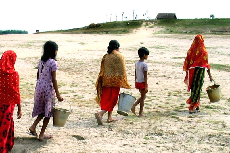Women carry empty buckets to fetch water from river as water crisis prevails in Malda district of West Bengal on May 14, 2014.