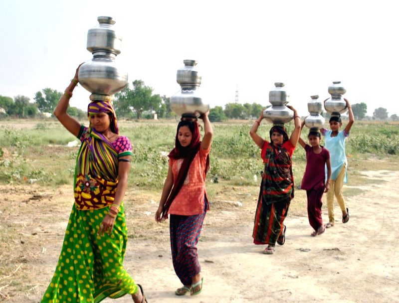 Women carry vessels on their head to fetch potable water on a hot day in Asgarpur village of Mathura on April 26, 2017.
