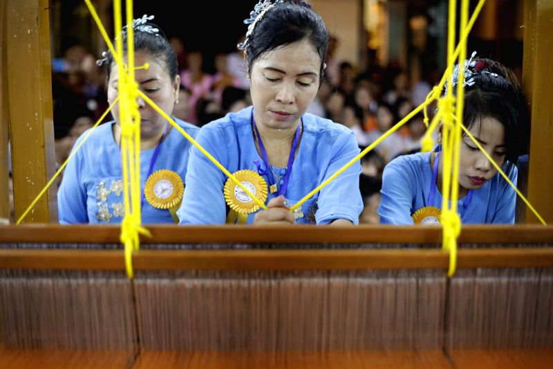 Women compete weaving robes at Shwedagon Pagoda in Yangon, Myanmar, Nov. 25, 2015. The weaving ceremony started from evening onwards till completion at dawn for ...
