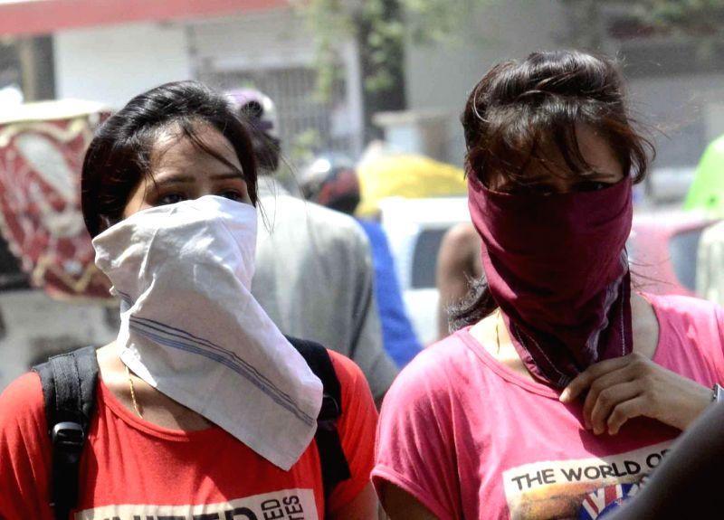 Women cover their face to avoid direct sunlight on a hot afternoon in Patna on May 13, 2014.
