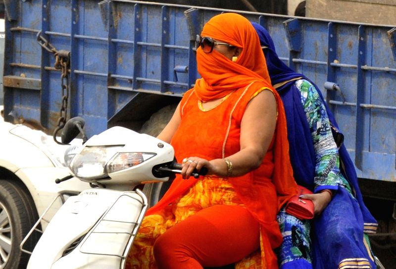 Women cover their faces so as to avoid scorching sun in Amritsar on May 9, 2017.