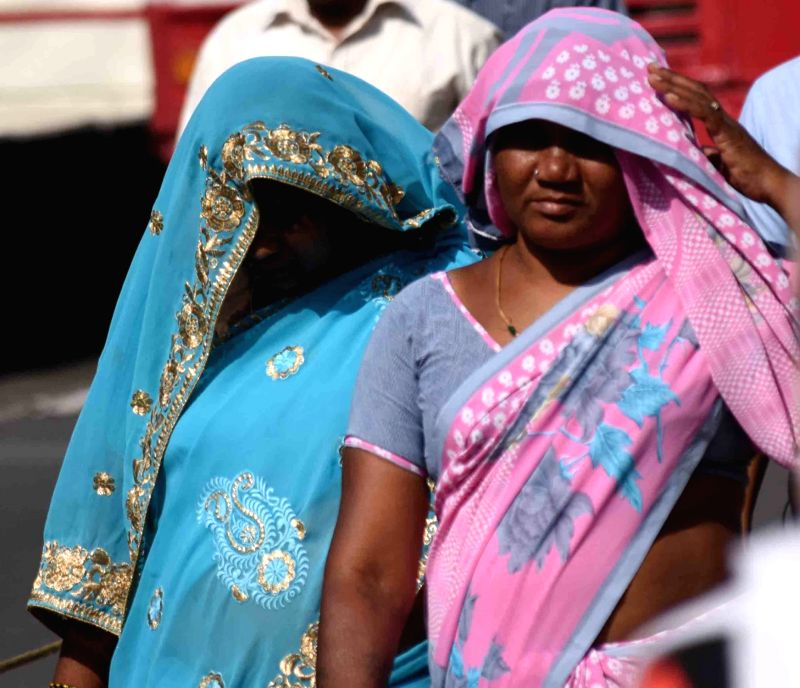 Women cover their faces to avoid scorching sun on a hot day in Hyderabad on March 25, 2017.