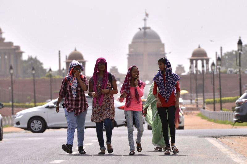 Women cover their faces to avoid scorching sun on a hot day in New Delhi on June 6, 2017.