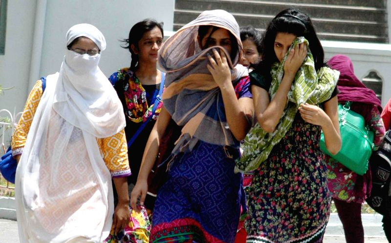 Women cover themselves to avoid direct sunlight on a hot afternoon in Patna on May 12, 2014.