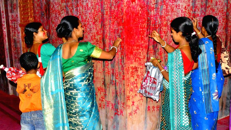 Women draw religious symbols with vermilion on a wall of a temple during Ambubachi festival, also known as Ambubasi festival in Agartala on June 24, 2014.