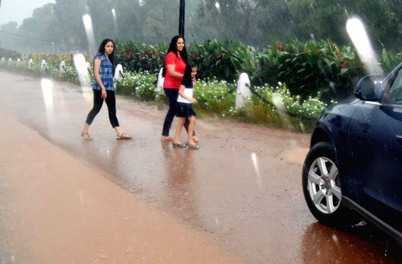 Women enjoy rains at India Gate, in New Delhi, on Aug 10, 2018.