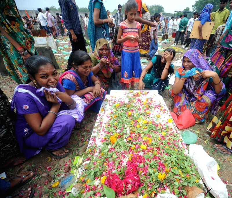 Women from Devipujak community cries as she sits near the decorated grave of a relative. Relatives bring gifts for the deceased during an annual festival in Ahmedabad on July 26, 2014.