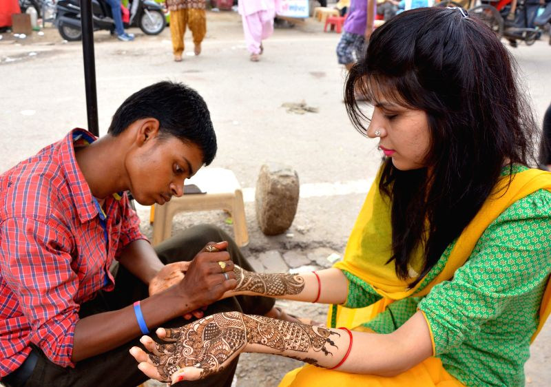 Women get her hand decorated with henna on the eve Teej Festival in Jaipur on July 29, 2014.