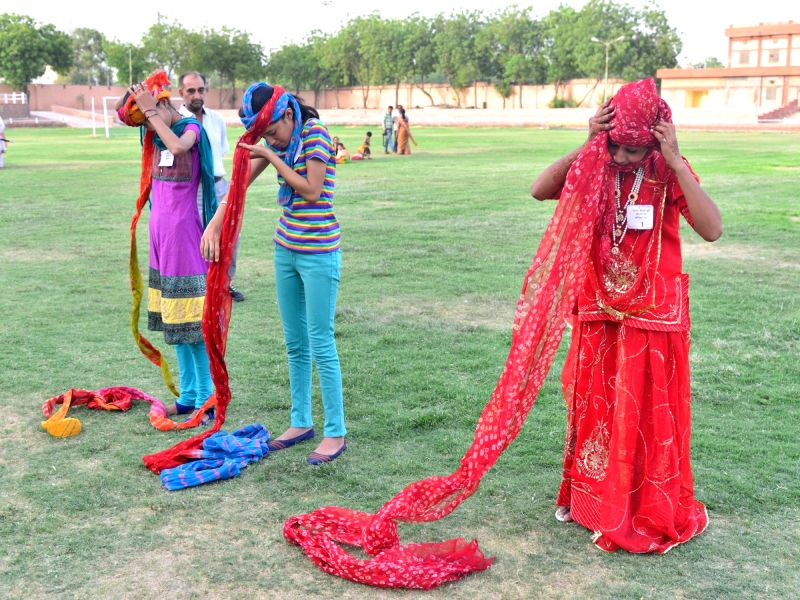 Women participate in a turban tying competition during 558th Foundation Day of Jodhpur on May 12, 2016.