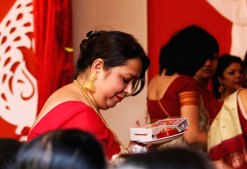 Women participate in Sindoor Khela - a ritual in which married woman apply vermilion to goddess Durga and thereafter to each other on the last day of Durga Puja - in New Delhi on Sept 30, ...