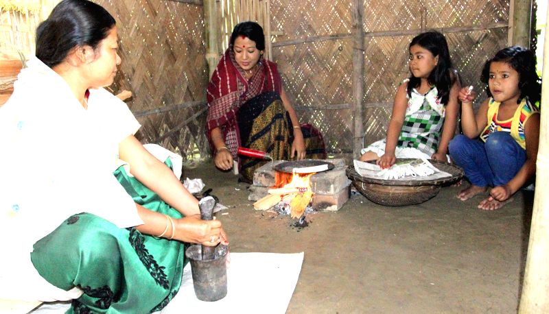 Women prepare rice cakes on Bohag Bihu at Tengakhat village in Dibrugarh  district of Assam on April 14, 2014.