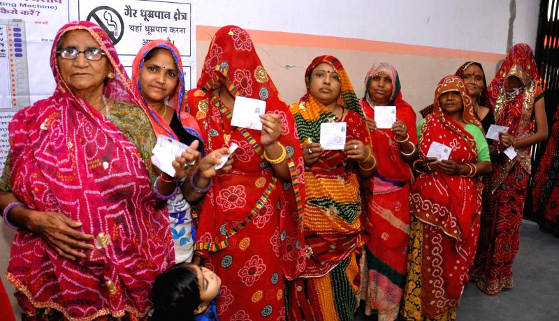 Women queue-up to cast their votes at a polling booth during the fifth phase of 2014 Lok Sabha Polls in Jaipur on April 17, 2014.