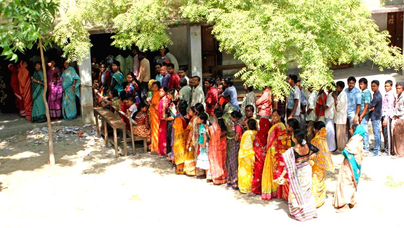 Women queue-up to cast their votes at a polling booth to cast their votes during the sixth phase of 2014 Lok Sabha Polls in Balurghat of West Bengal's  South Dinajpur district on April 24, 2014.