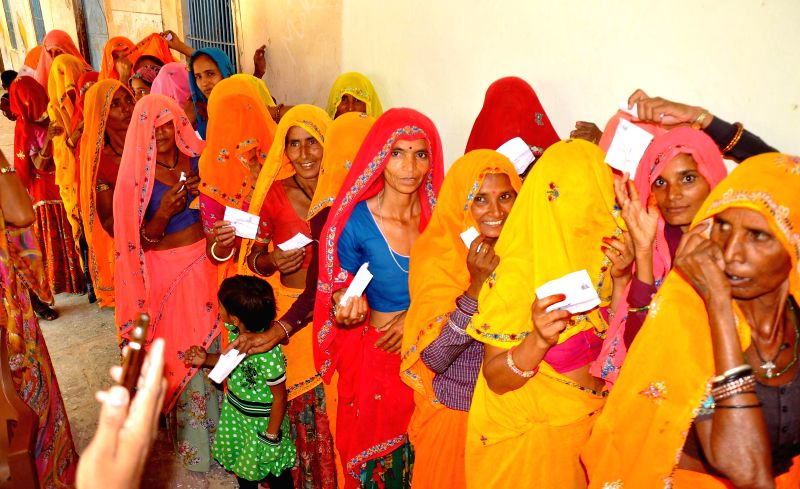 Women queue-up to cast their votes at a polling booth during the sixth phase of 2014 Lok Sabha Polls at a village in Dausa district of Rajasthan on April 24, 2014.