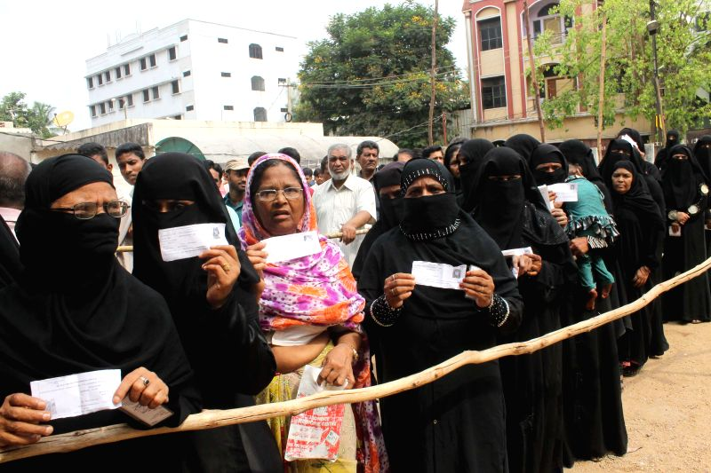 Women queue-up to cast their votes at a polling booth during the seventh phase of 2014 Lok Sabha Polls in Hyderabad on April 30, 2014.