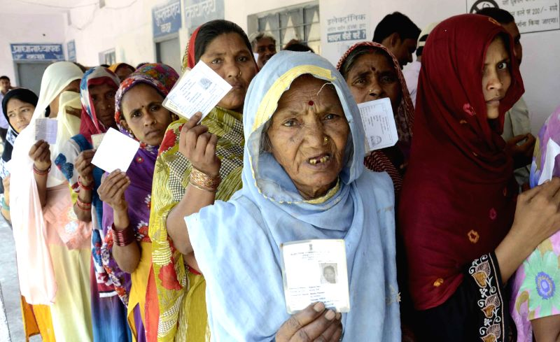 Women queue-up to cast their votes at a polling booth during the eighth phase of 2014 Lok Sabha Polls in Hajipur of Bihar on May 7, 2014.