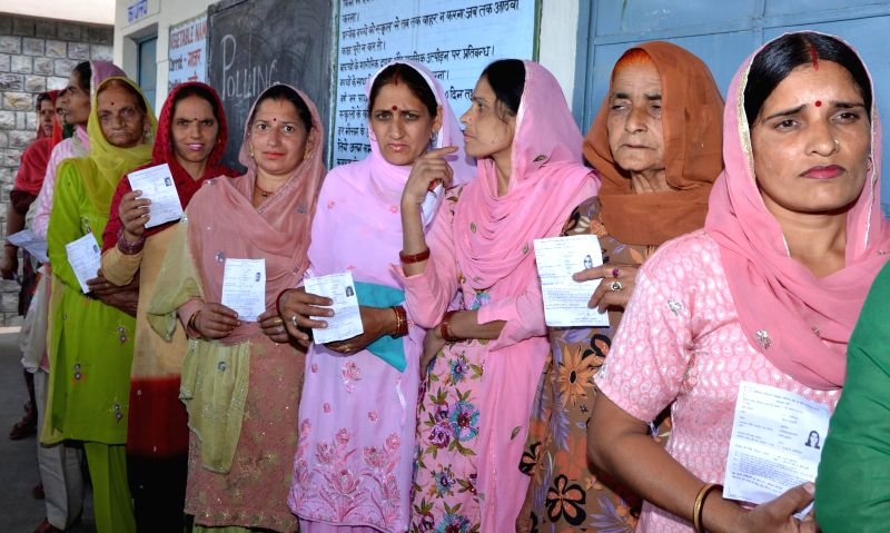 Women queue-up to cast their votes at a polling booth during the eighth phase of 2014 Lok Sabha Polls  in Hamirpur of Himachal Pradesh on May 7, 2014.