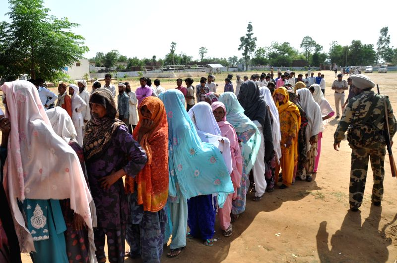 Women queue-up to cast their votes at a polling booth during 2014 Lok Sabha Polls re-elections in Mewat district of Haryana on May 15, 2014.