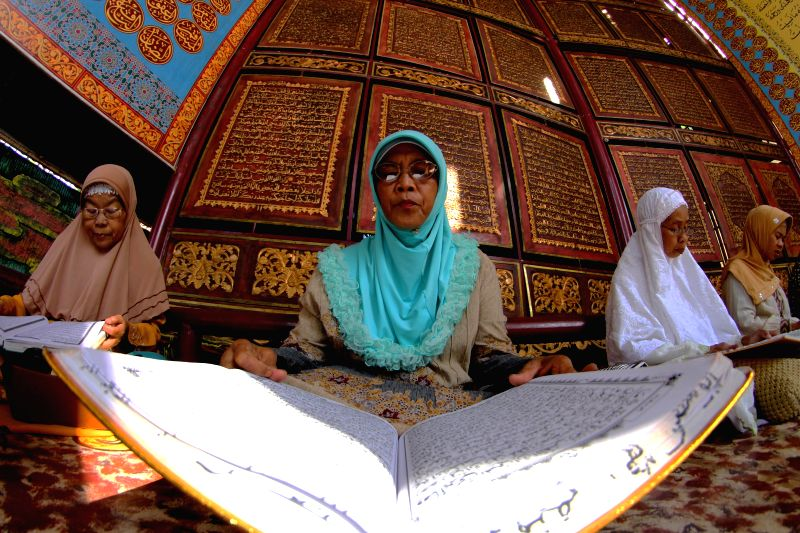 Women read Koran during the Nuzul Al-Quran in Palembang, Indonesia, July 4, 2015. Nuzul Al-Quran is celebrated on the 17th day of Ramadan to mark the first ...