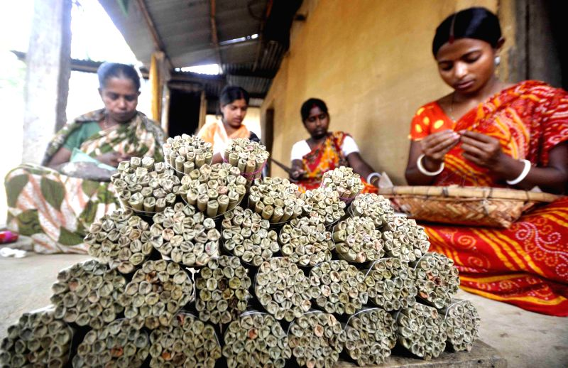 Women roll beedis (tobacco flake hand rolled in tendu leaf) in their courtyard even on International Workers' Day which is celebrated worldwide on 1st May to commemorate historic struggle of workers .