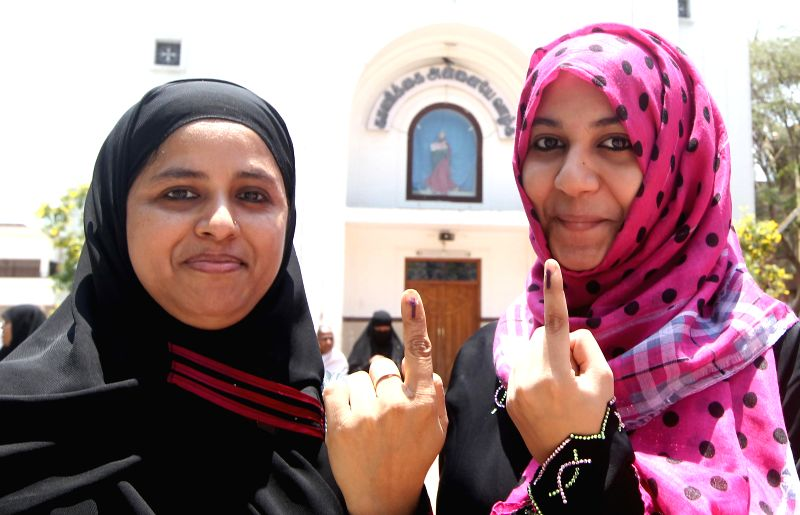 Women show their fore fingers marked with phosphorous ink after casting their votes at a polling booth during the sixth phase of 2014 Lok Sabha Polls in Chennai on April 24, 2014.
