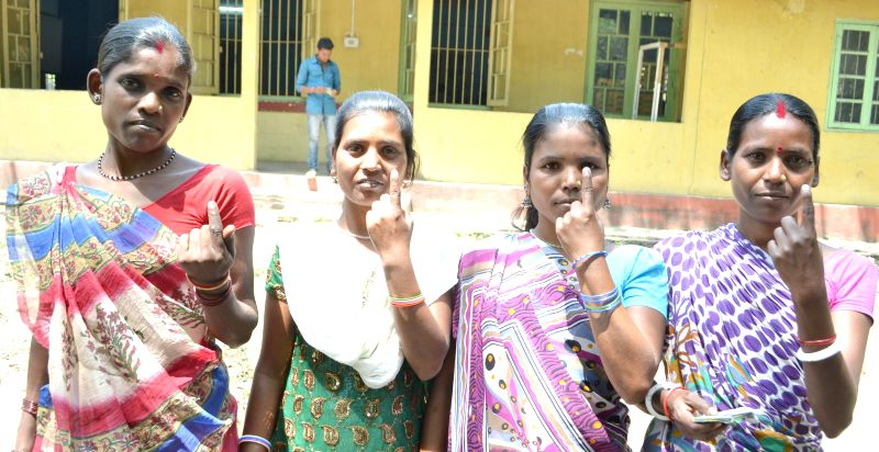 Women show their fore fingers marked with phosphorous ink after casting their votes at a polling booth during the sixth phase of 2014 Lok Sabha Polls in Guwahati on April 24, 2014.