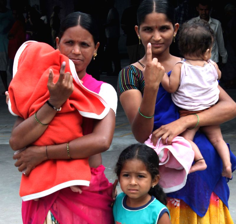 Women show their fore fingers marked with phosphorous ink after casting their votes at a polling booth during the seventh phase of 2014 Lok Sabha Polls in Hyderabad on April 30, 2014.