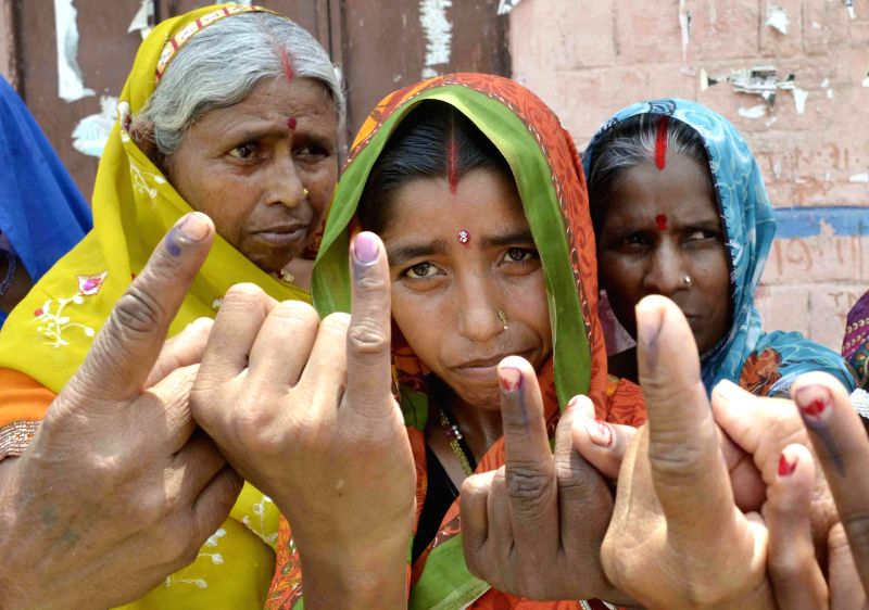 Women show their fore fingers marked with phosphorous ink after casting their votes at a polling booth during the seventh phase of 2014 Lok Sabha Polls in Samastipur of Bihar on April 30, 2014.