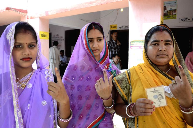 Women show their fore fingers marked with phosphorous ink after casting their votes at a polling booth during the eighth phase of 2014 Lok Sabha Polls in Hajipur of Bihar on May 7, 2014.