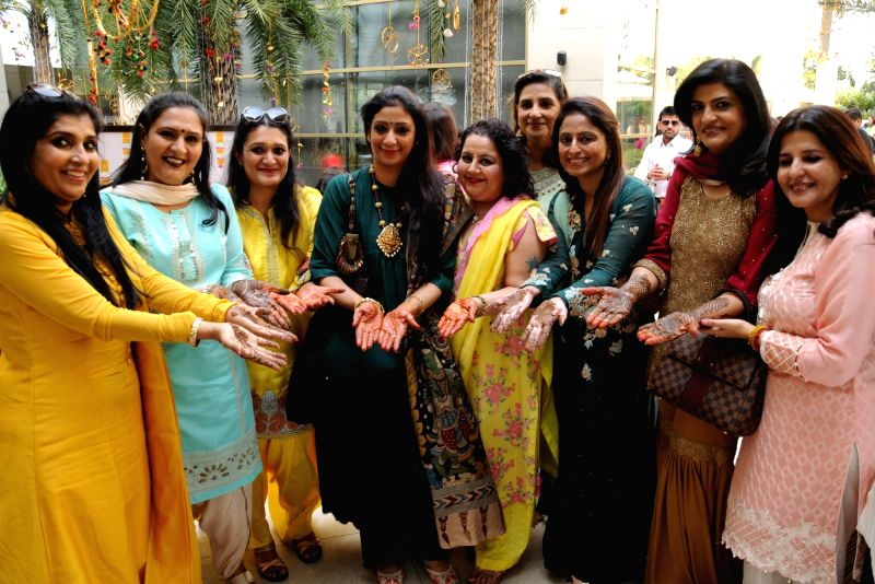 women get decked up with mehndi on their hands