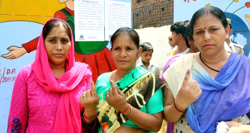 Women show their show their forefingers marked with phosphorous ink after casting vote at a polling booth during Municipal Corporation of Delhi (MCD) Polls in New Delhi, on May 15, 2016.