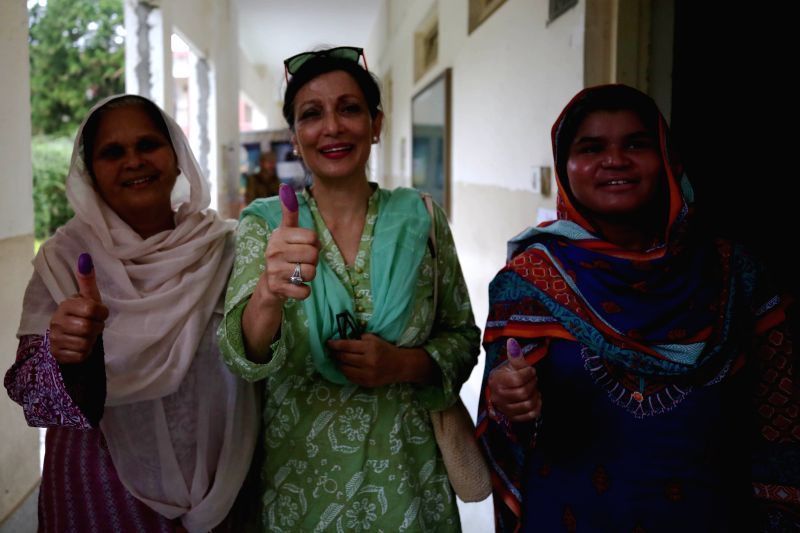 : Women show their thumbs after casting vote at a polling station during Pakistan's general elections in Islamabad, capital of Pakistan, on July 25, 2018. ...