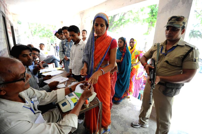 Women show their voter's identity card at a polling booth during the ninth phase of 2014 Lok Sabha Polls in Vaishali district of Bihar on May 12, 2014.