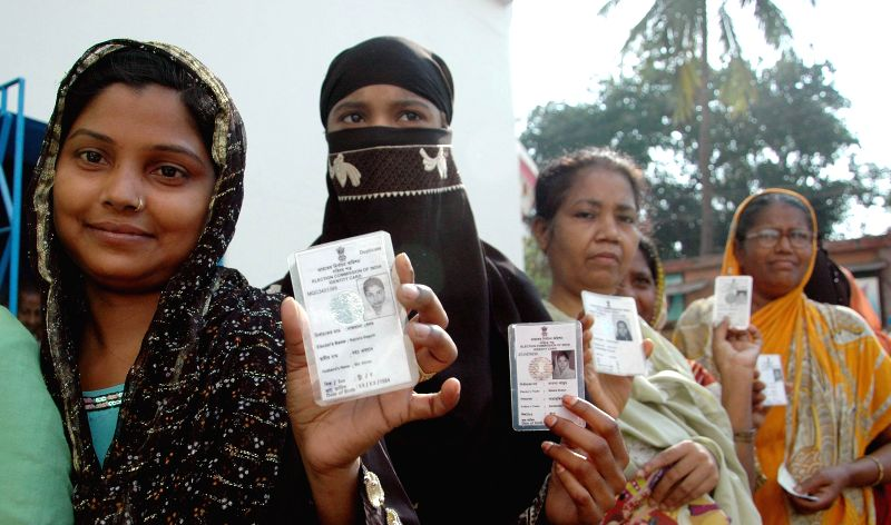 Women show their voters' identity card after casting their votes at a polling booth during the seventh phase of 2014 Lok Sabha Polls in Howrah of West Bengal on April 30, 2014.