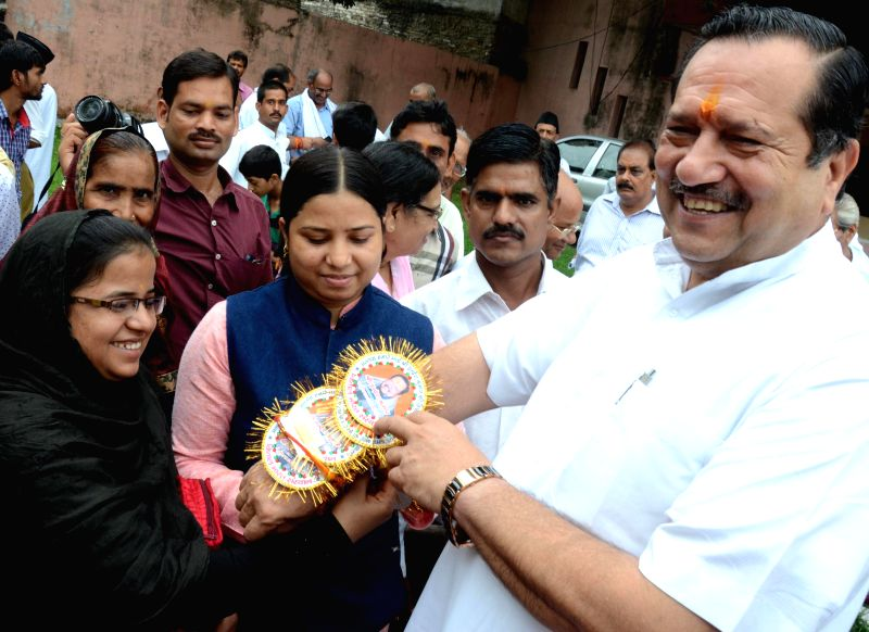 Women tie `rakhi` on the wrist of RSS leader Indresh Kumar on Raksha Bandhan in Lucknow on Aug 10, 2014.