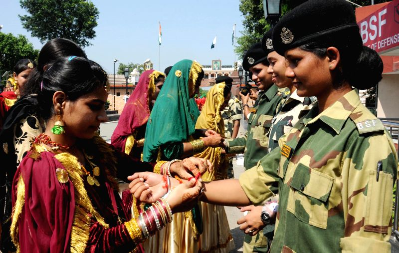 Women tie Rakhis to the soldiers deployed at Wagha border on Raksha Bandhan on Aug 10, 2014.