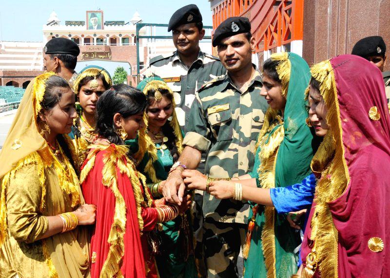 Women tie Rakhis to the soldiers deployed at Wagha border on Raksha Bandhan on Aug 10, 2014.