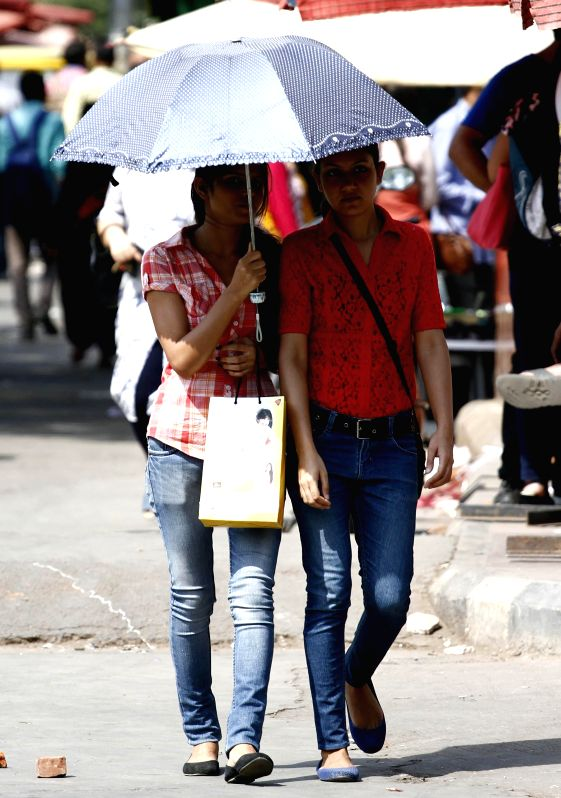 Women use umbrella to shield themselves from scorching heat in New Delhi on April 29, 2014.