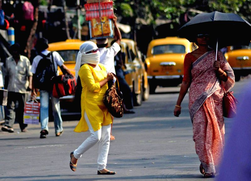 Women use umbrellas and clothes to avoid direct Sunlight on a hot afternoon in Kolkata on May 15, 2014.