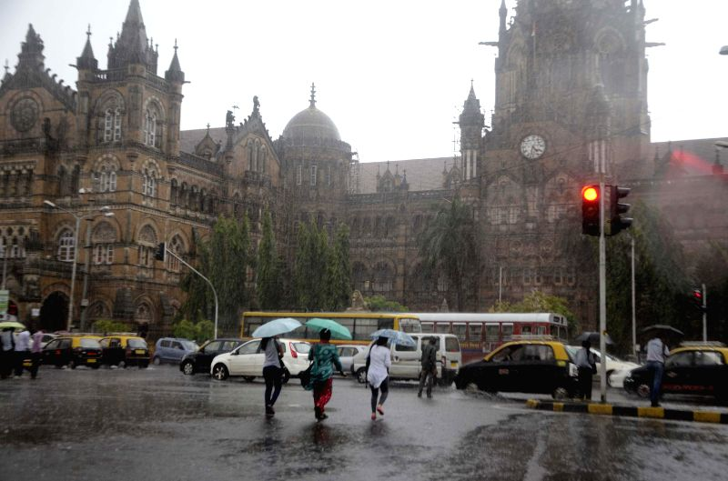 Women use umbrellas to shield themselves from rains at CST in Mumbai on July 10, 2014.