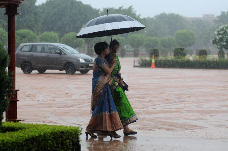 Women use umbrellas to shield themselves from getting drenched during heavy rains in New Delhi on Aug 10, 2014.