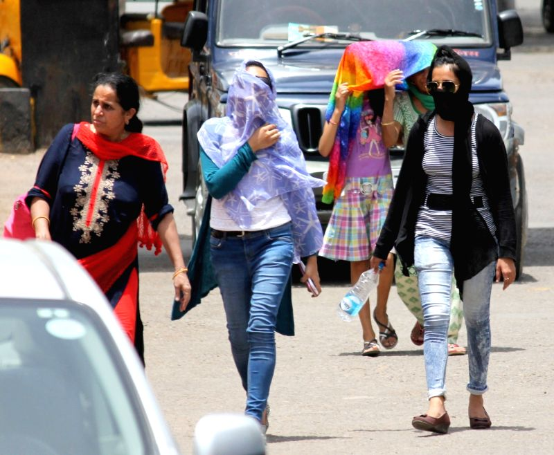 Women walk with their faces covered on a hot day in Mathura on June 5, 2017.