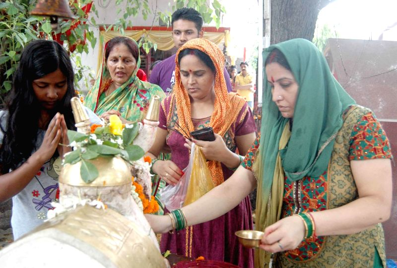 Women worship lord Shiva at a Patna temple during the holy month of Sawan on July 21, 2014.