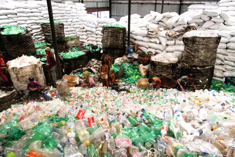 Workers arrange waste polyethylene terephthalate (PET) bottles at the factory in Dhaka, Bangladesh on June 3, 2016.
