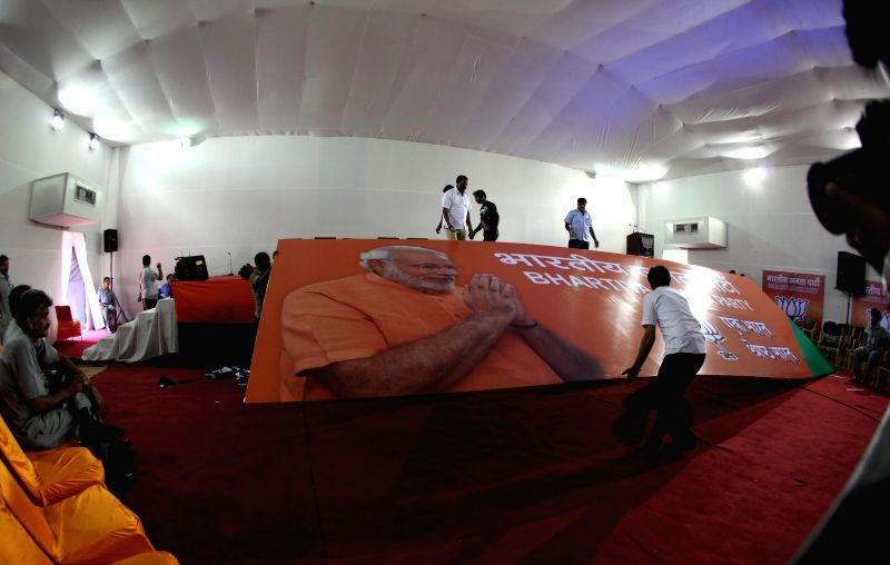 Workers busy putting up a hoarding at BJP headquarters before a press conference in New Delhi on May 17, 2014.